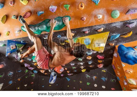 Young man bouldering in indoor climbing gym trying to solve challenging problem