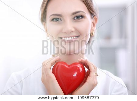 Female doctor with stethoscope holding heart, isolated on white background