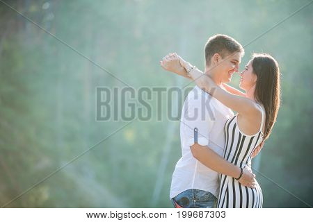 Happy young couple kissing outdoors on summer day
