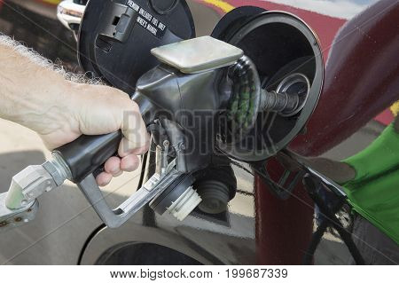 Hand of man holding gas station nozzle pumping fuel into black vehicle.