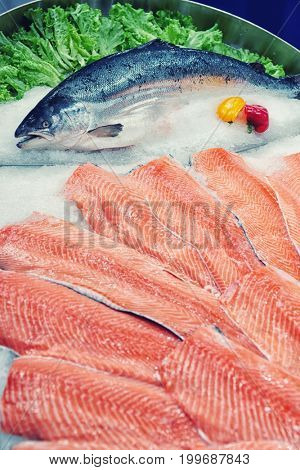 Fresh salmon, fillet and whole, on ice display in supermarket, toned image