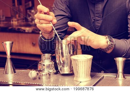 Bartender is mixing ingredients in metal shaker with bar spoon, toned image