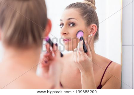 Woman powdering her face with cosmetic brush in front of bathroom mirror