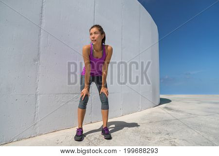 Runner woman tired resting catching breath during cardio workout. Motivation and determination athlete girl ready to run.