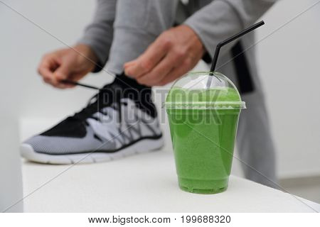 Green smoothie man tying running shoes laces ready to run in urban city. Healthy active lifestyle, closeup of trainers.