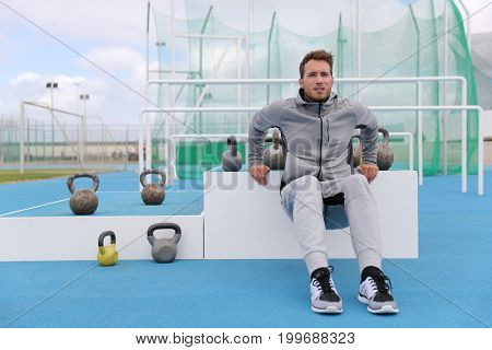 Gym fitness man training arms muscles doing triceps dips at outdoor training centre at stadium. Sport athlete in sweatpants sportswear outside.