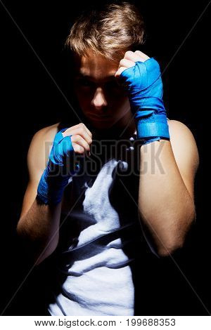 Photo of muscular teenager boxing on black background.