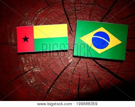 Guinea Bissau Flag With Brazilian Flag On A Tree Stump Isolated