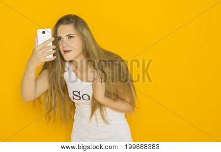 Unhappy young attractive woman very surprised something on her smartphone. Funny girl with mobile phone reads message. Studio shot orange background
