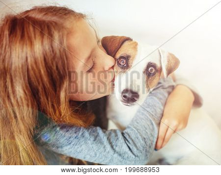 Happy child with dog. Portrait girl with pet. Teen kiss Jack Russell