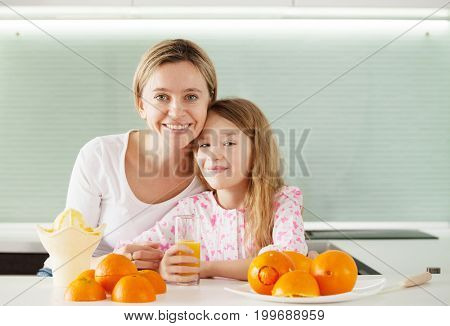 Mother and daughter make orange juice on a juicer