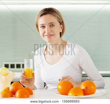 Woman cooking orange juice on juicer