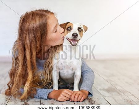 Happy child with dog. Portrait girl with pet. Teen kissing Jack Russell