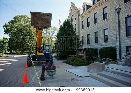 JOLIET, ILLINOIS / UNITED STATES - JULY 19, 2017: A Gehl RS6-42 Telescopic Handler is parked in front of the historic Welcome Center at the University of Saint Francis.