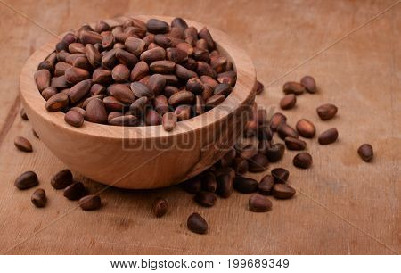 Bowl of cedar nuts on wooden background