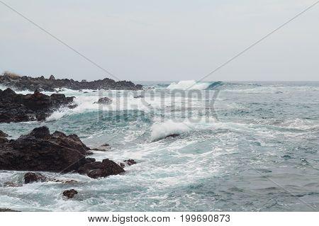 Pacific Ocean coastline in Hawaii on a grey cloudy day