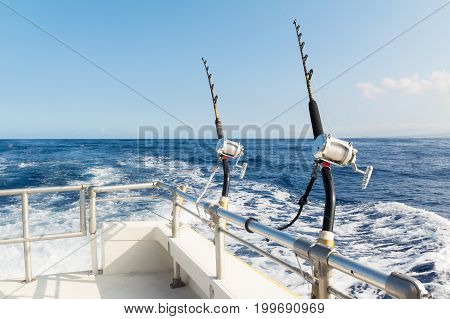 Two rods and reels in holders on charter boat rails on a sunny day with blue sky.