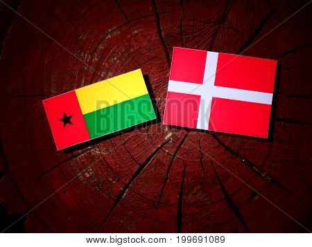Guinea Bissau Flag With Danish Flag On A Tree Stump Isolated