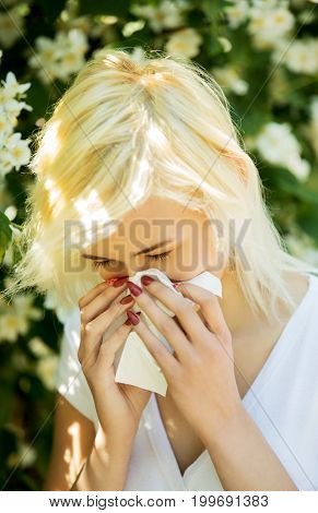 Portrait of a young blonde woman blowing her nose when standing close to flowers in a park