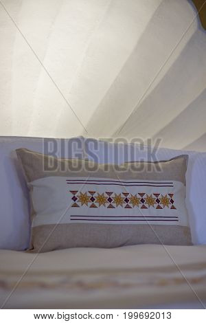 Some clean bedding linens with patterned pillow.