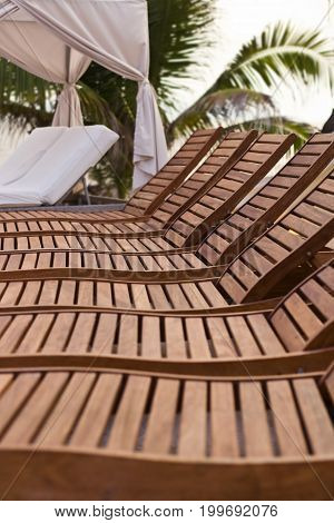 A row of wooden lounge chairs by a pool.