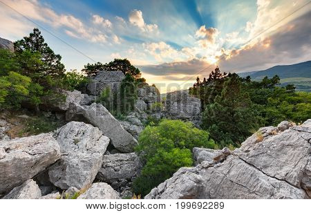A pile of stones on the mountain among the trees and bushes in the background of the setting sun through the clouds