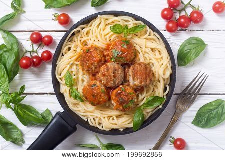 Spaghetti in pan with meatballs and basil . Top view