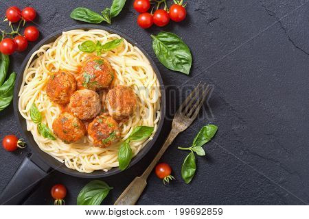 Spaghetti in pan with meatballs and basil . Top view space for text