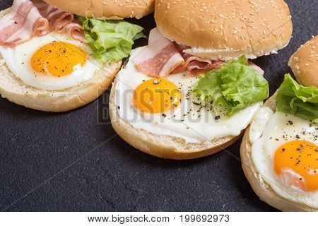 Sandwich with eggs and bacon on wooden table copy space
