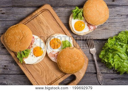 Sandwich with eggs and bacon on wooden table top view