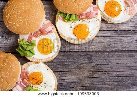Sandwich with eggs and bacon on wooden table top view copy space