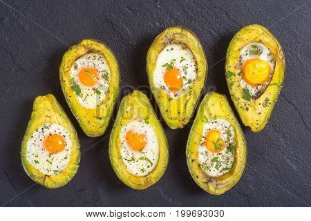 Baked avocado with eggs on woode background top view