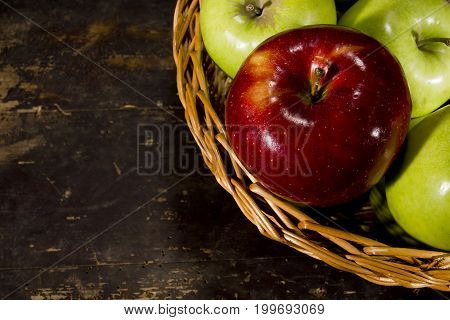 Multicolored apples in a wicker basket on a vintage background