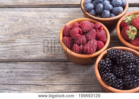 berries : raspberries blueberries blackberries strawberries in a bowl . space for text