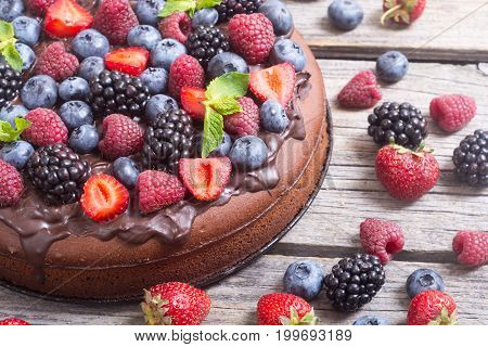Homemade chocolate cake with summer berries and mint .