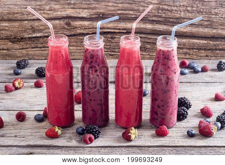 Fresh homemade smoothies with berries on rustic background .