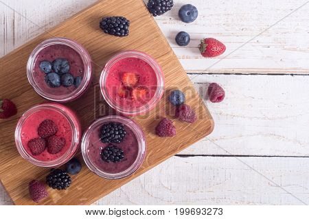 Fresh homemade smoothies with berries on rustic background . Top view copy space