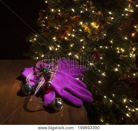 Pink gloves under bells for a Christmas present next to the tree