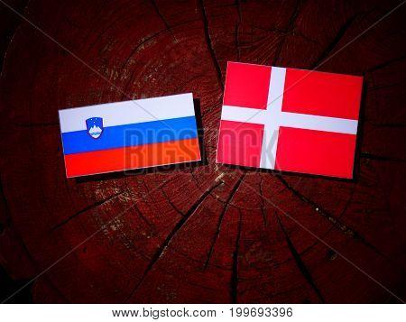 Slovenian Flag With Danish Flag On A Tree Stump Isolated
