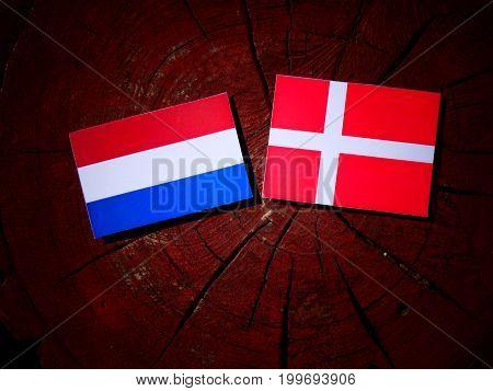 Dutch Flag With Danish Flag On A Tree Stump Isolated