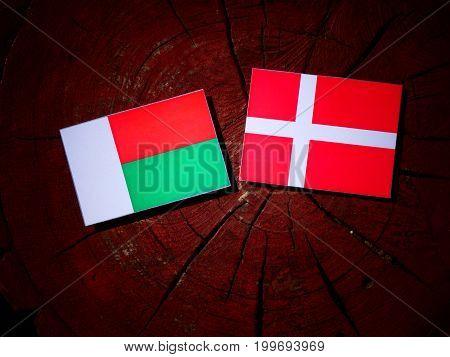 Madagascar Flag With Danish Flag On A Tree Stump Isolated