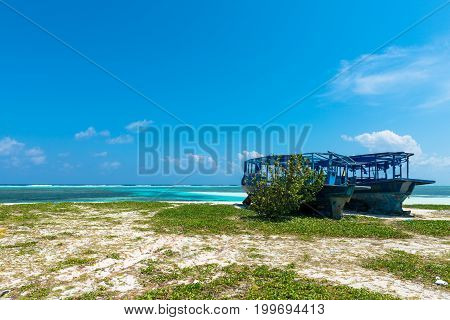 Wide angle picture from the beach of blue shipwrecked and turquoise water during a sunny day in Maafushi Maldives.