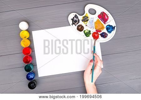 Artist's hand holds the brush over a blank sheet of white paper near open cans of colored paints and palette on grey wooden board and ready to paint with watercolors.