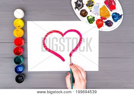 Artist's hand draws heart on sheet of white paper near open cans of colored paints and palette on grey wooden board