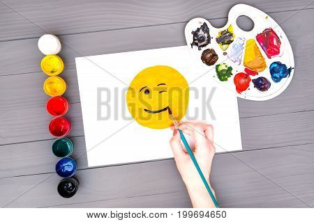 Artist's hand draws smile on sheet of white paper near open cans of colored paints and palette on grey wooden board