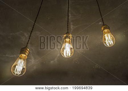 Hanging light bulbs over oxide dark color concrete background. Closeup