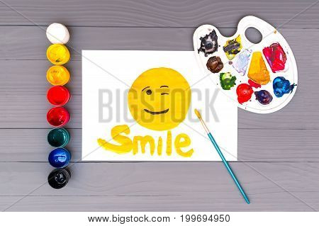 Painted smile with the inscription smile on sheet of white paper near open cans of colored paints, brush and palette on grey wooden board