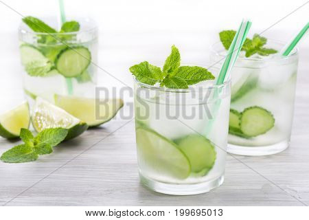 Healthy vitamin drink with cucumber, lime and mint on a wooden background
