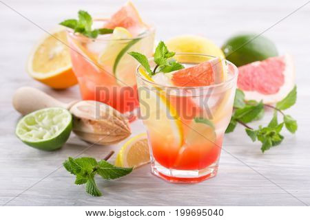 Homemade cold citrus lemonade with mint on a light wooden background