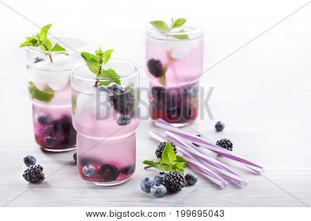 Cold refreshing drink made of berries on a light background. Blackberries, blueberries and mint
